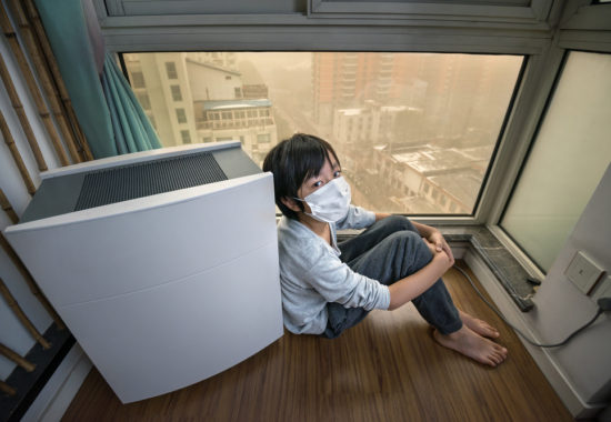 Boy staying home near air purifier