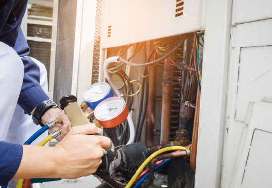 Qualified technician checking air conditioner